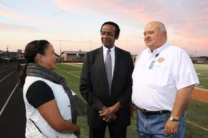 Woman and two men talking on football field