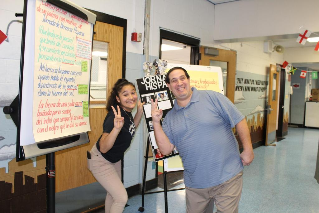 female student with Mr. Spano each holding the peace sign