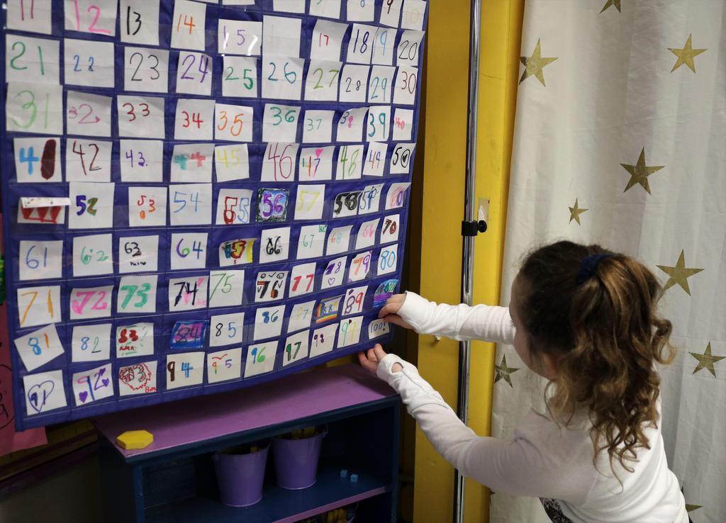 Photo of Tamaques 1st grader putting the number 100 in a chart noting the first 100 days of school.