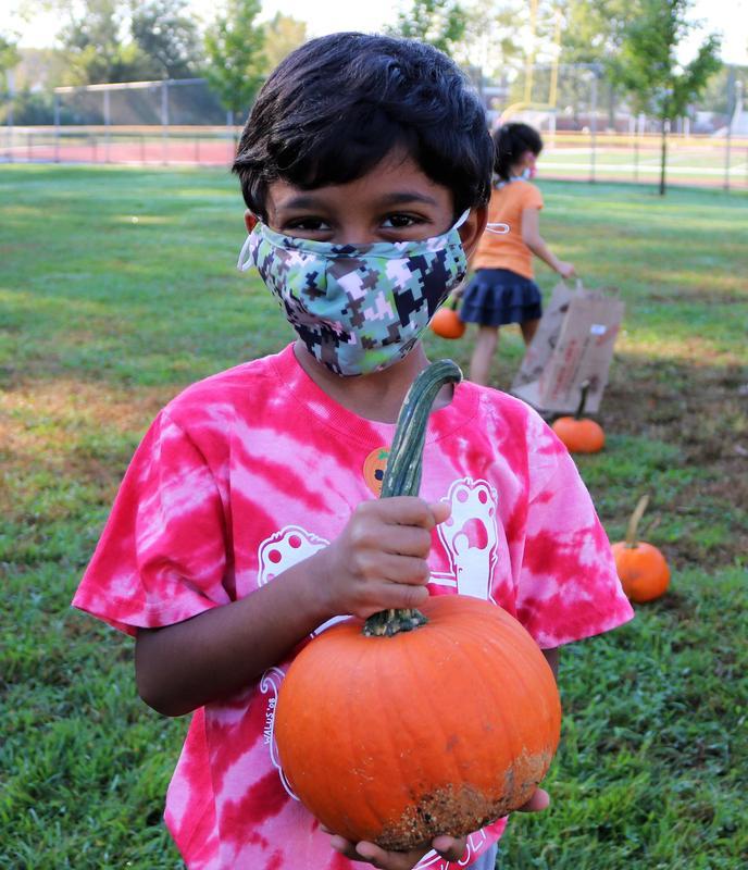 Photo of kindergartner holding pumpkin during annual Pumpkin Patch event.