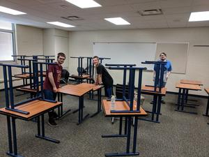 STEP students wipe down desks in a classroom.