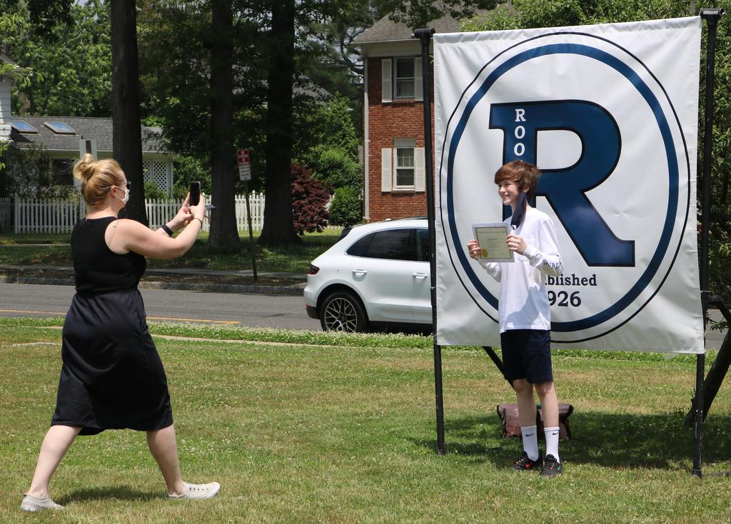 Photo of RIS 8th grader posing in front of R banner as mom takes photo