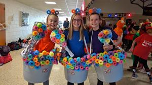 Three girls dressed as bowls of fruit loops.