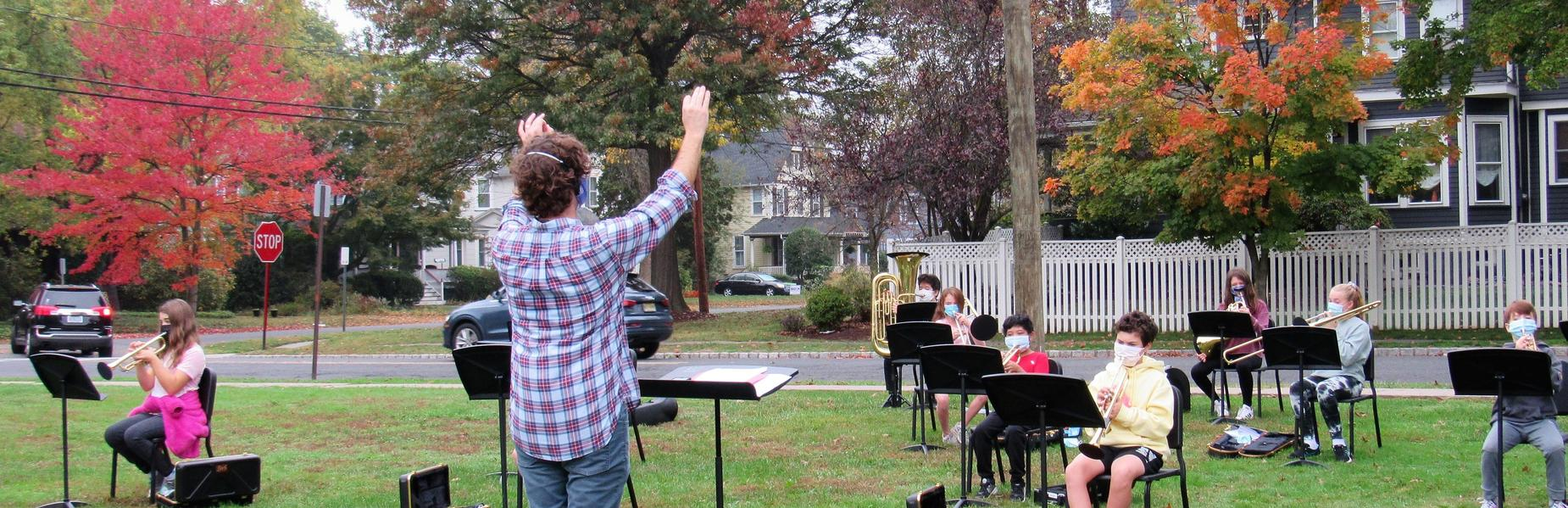 With brilliant autumn colors as a backdrop, Roosevelt Intermediate School Band Director James Doyle conducts/instructs student musicians.