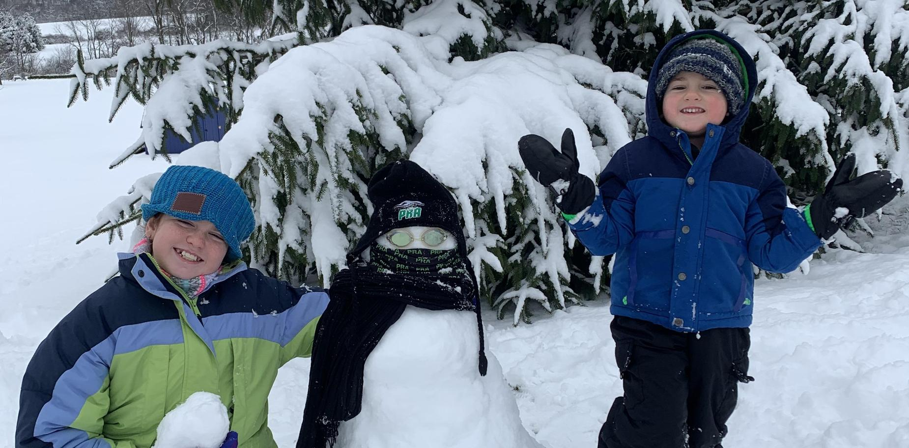 two kids and a snowman in the snow