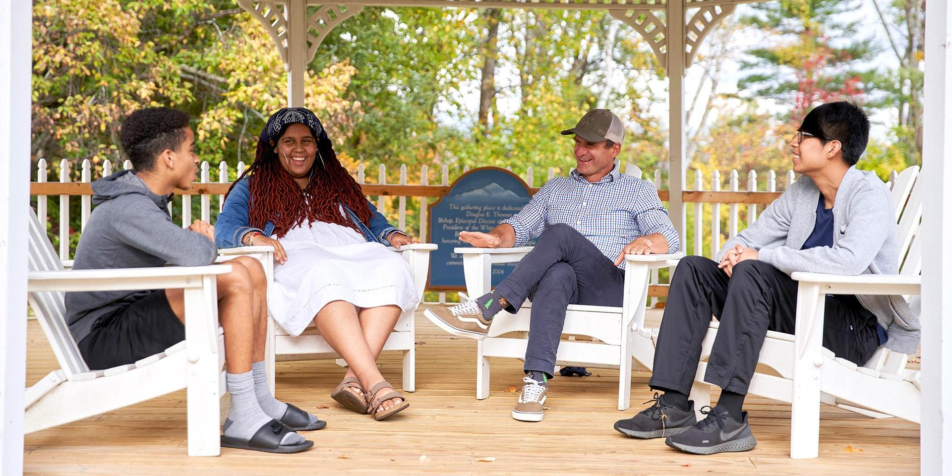 Students in The White Mountain Scholars Program chatting in the Theuner Gazebo with program director Matthew Toms.