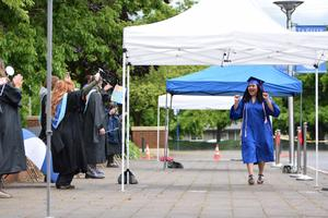 graduate walking down sidewalk