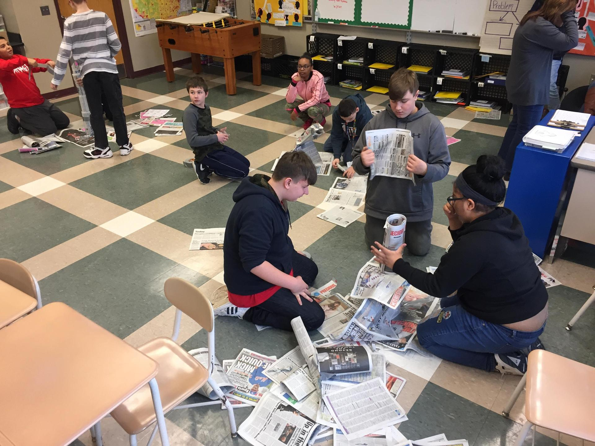 Students building newspaper towers in a competitive exercise.