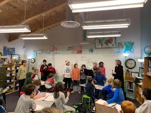 Middle School students singing to 4th Grade students