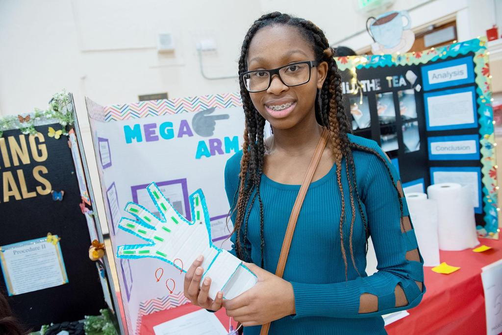 A student holds a cutout of a hand as she stands in front of her science fair project