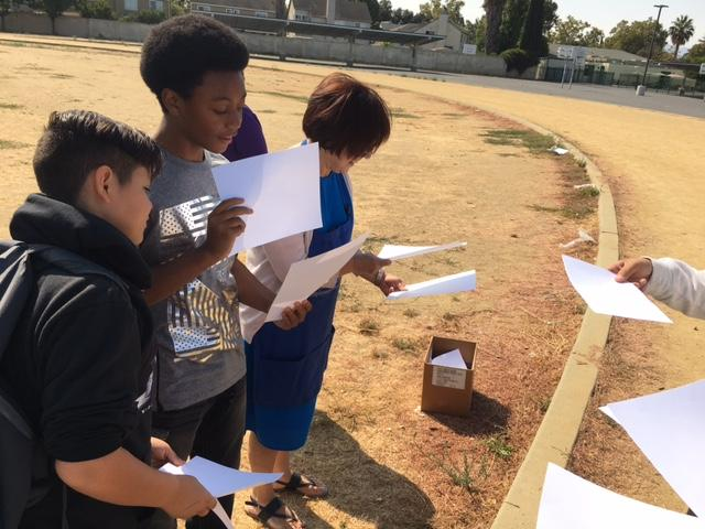 students and a teacher outside on a track looking at papers they are holding up to the sun to get an image of the eclipse
