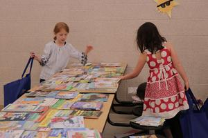 Two students choose books from a table.