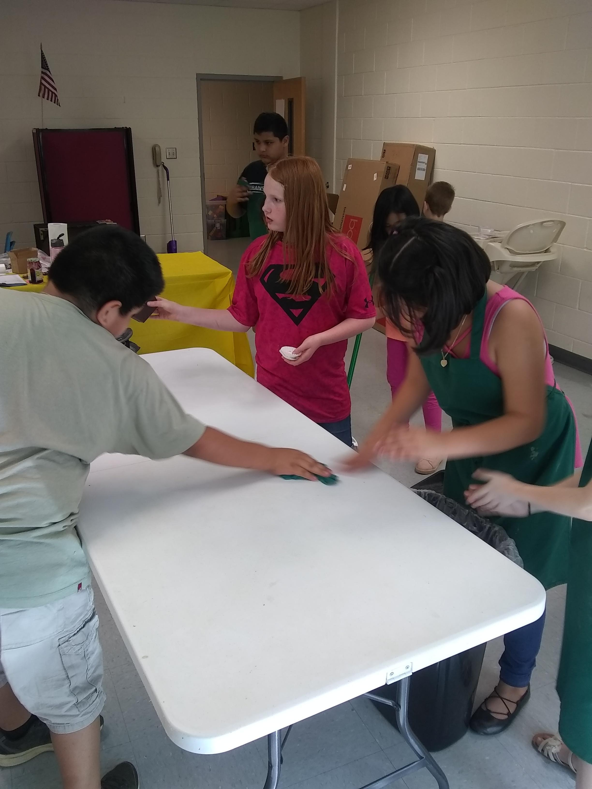 kids cleaning up tables and workroom