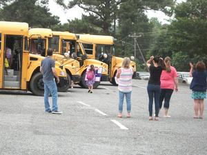Staff members gather in the bus parking lot.