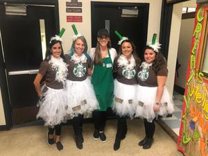 group of teacher dressed as starbucks barista & four frapuccino's