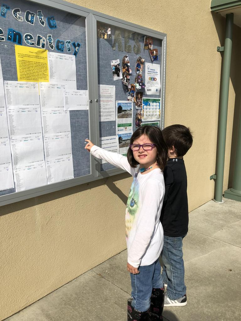 2 students finding their class on the list