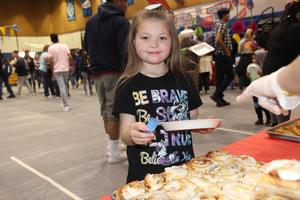 Young girl looking at tray of cinnamon rolls at Cultural Unity Fair