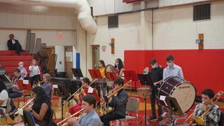 A group of students playing band instruments in the Benjamin gym