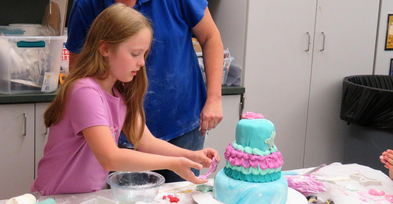 A Lee third-grader puts decorations on a cake.