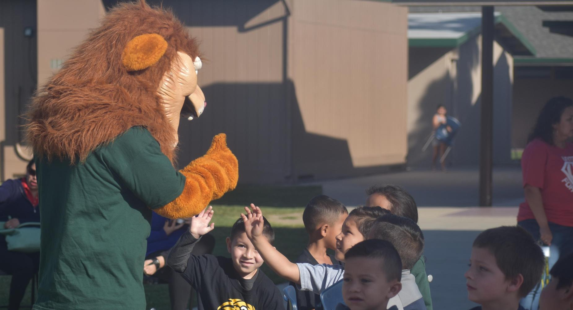 Lincoln Lion giving students high fives