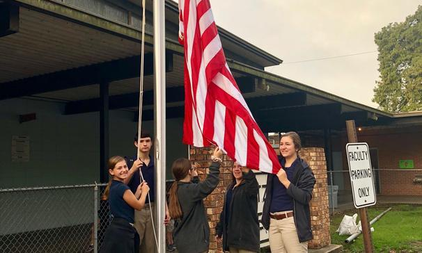 students raising flag