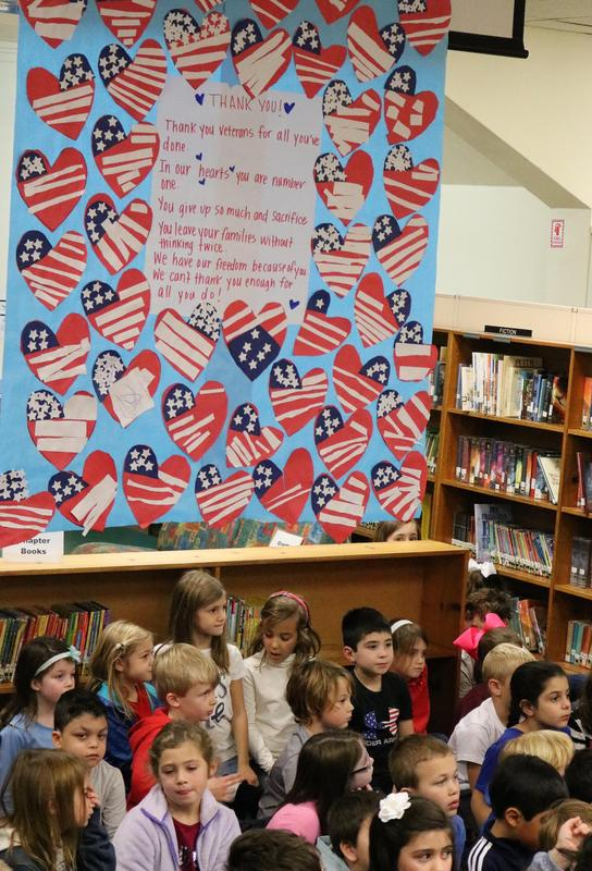 1st graders at McKinley in front of a larger poster containing a heartfelt poem and construction paper hearts welcoming veterans to their library on Veterans Day.