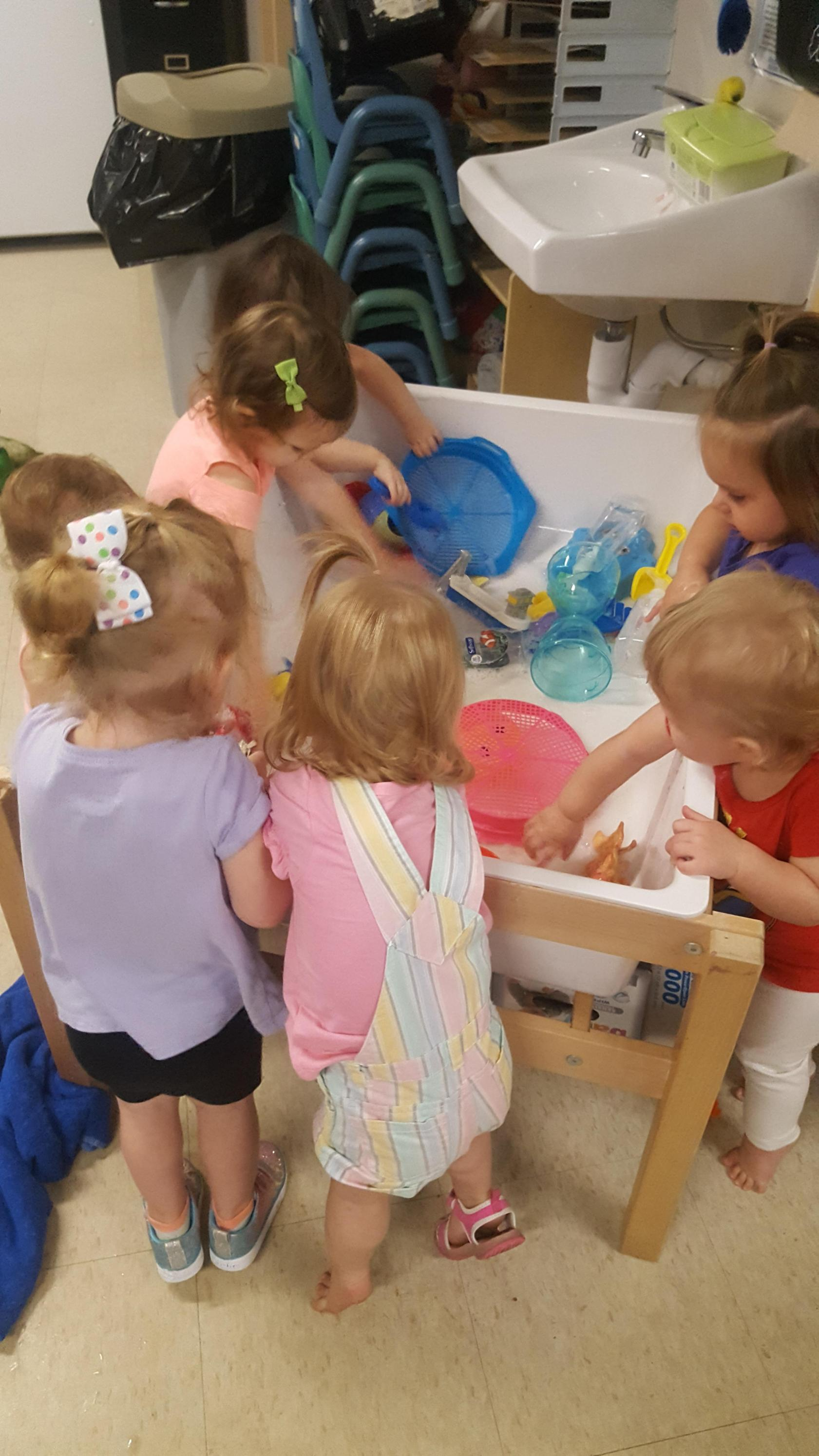 Children, from infant program, playing with toys in the special water tub table.