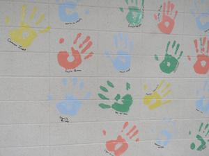 Colorful handprints decorate the wall.