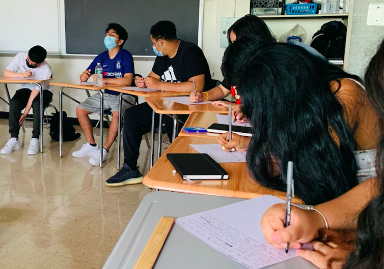 students writing at their desk