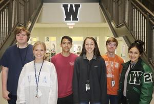 group of 6 students pose in front of lighted W