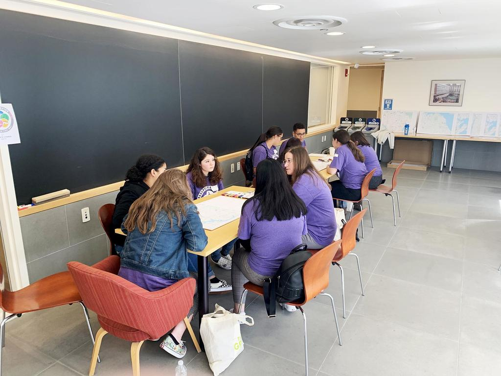 Students sit inside a classroom at the Harvard Science Center for the EHS students look at a group of photos at a large table during the EHS students work on a hands-on experiment during the Transportation YOU Boston Summit