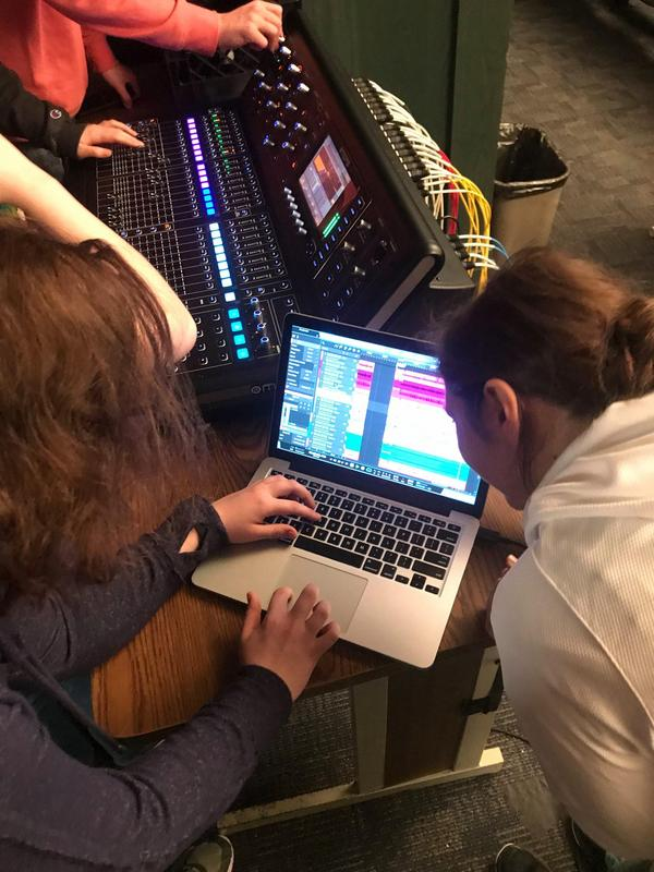 photo of students using a computer to adjust sound in an auditorium