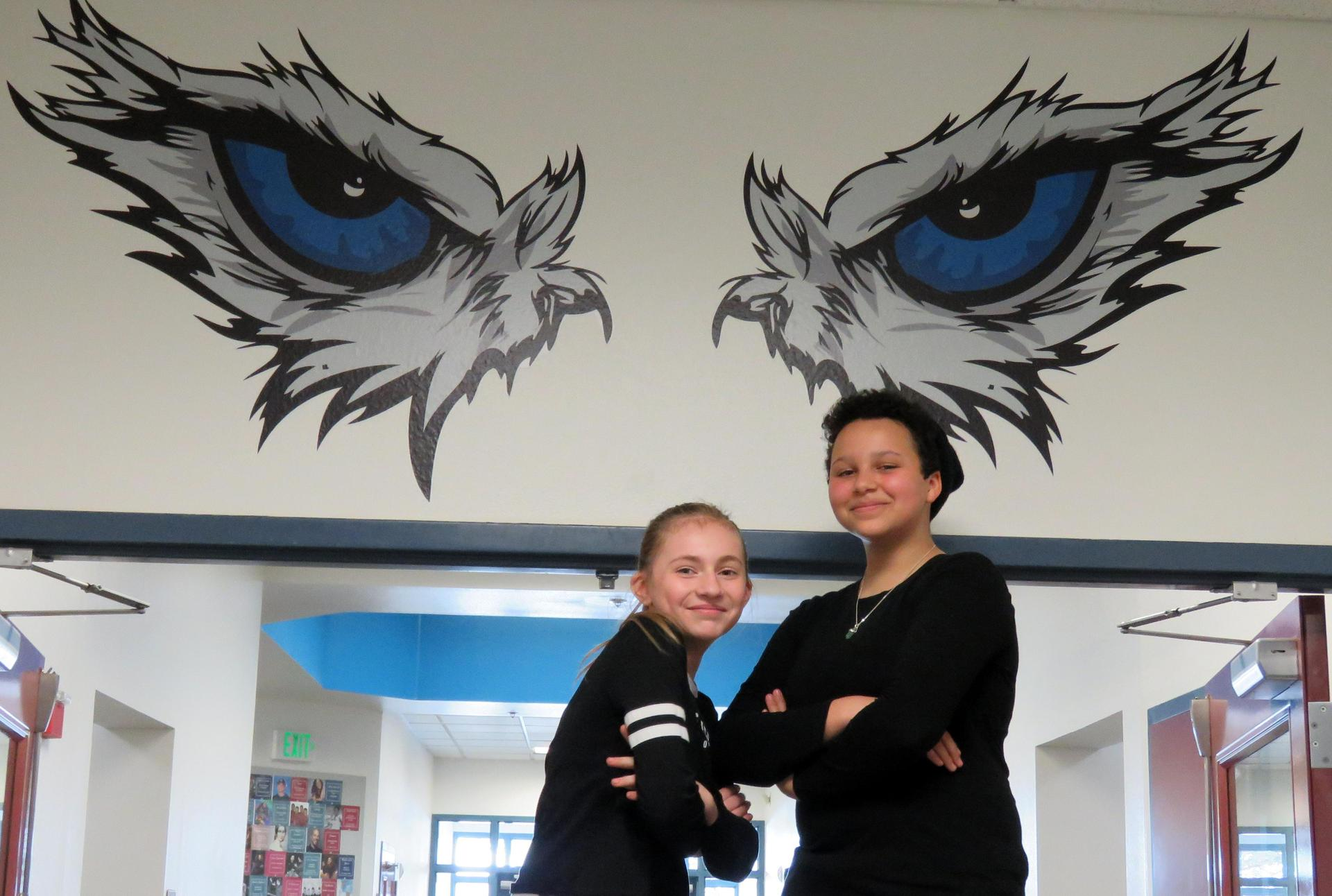 Two girls pose with folded arms under the Falcon Eyes painting on the walls at Park Ridge