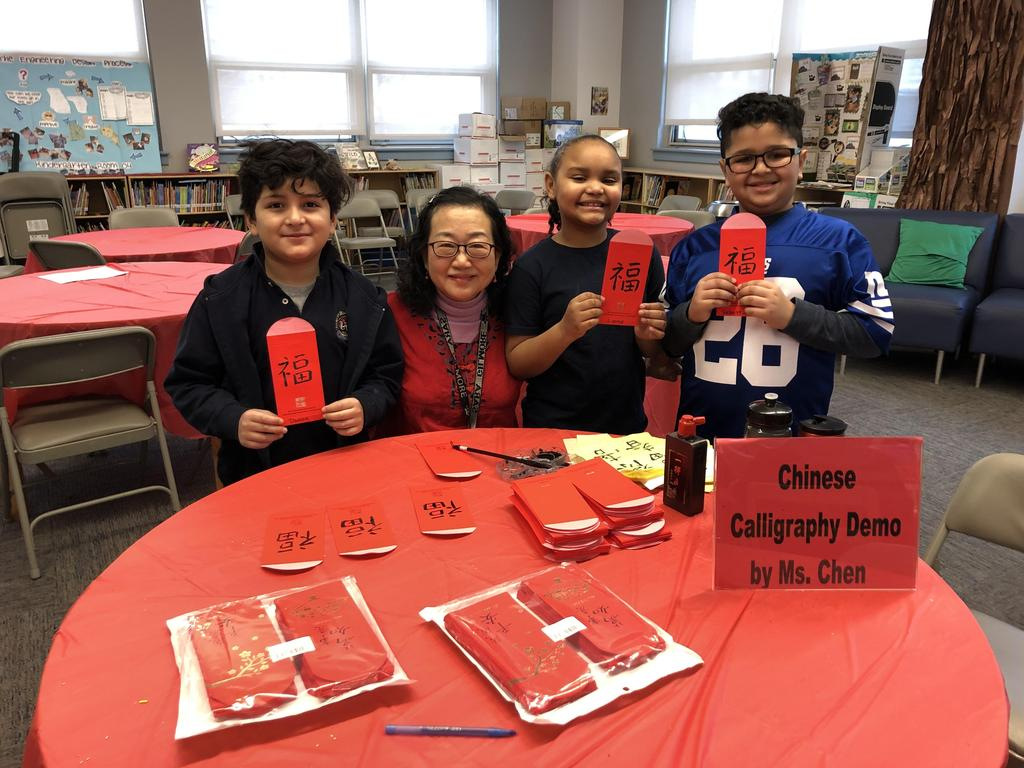 Ms. Chiang with three students holding up their names in Chinese