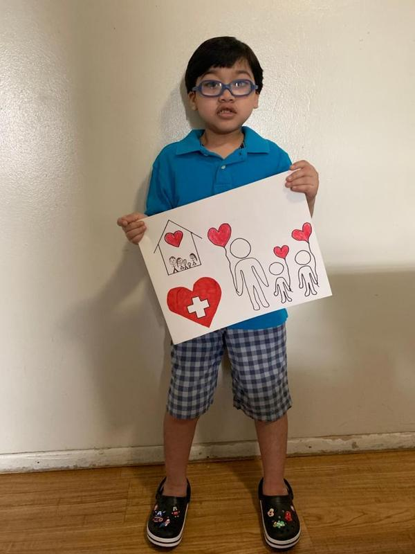 boy with glasses showing off his poster