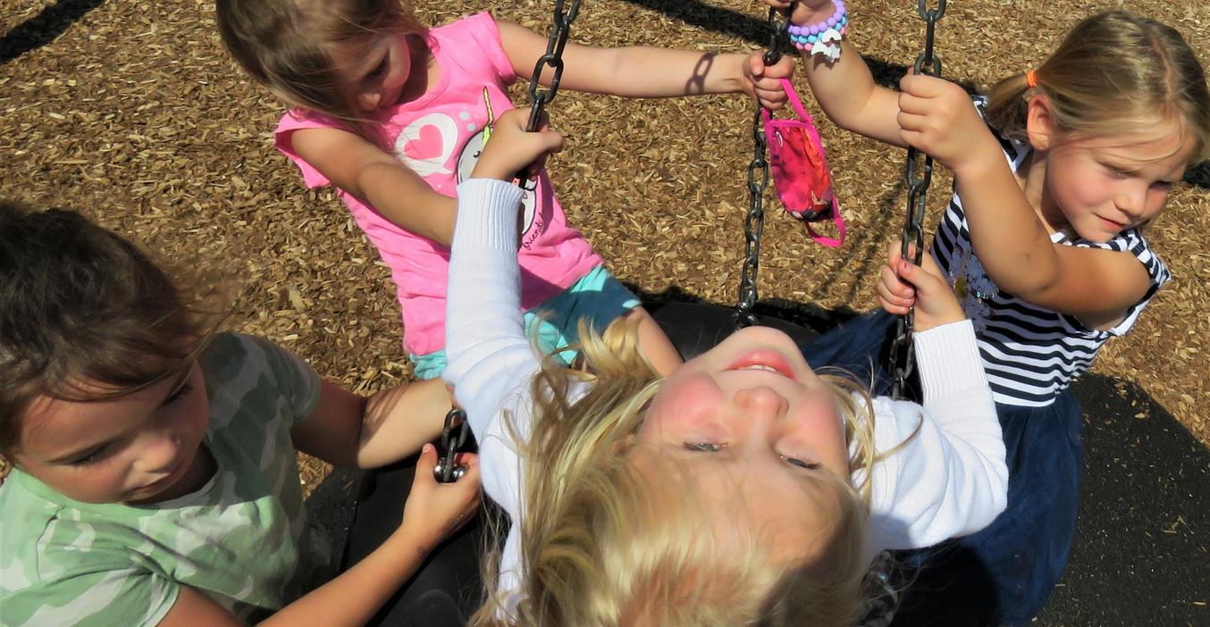 Four girls take turns on the swinging tire.