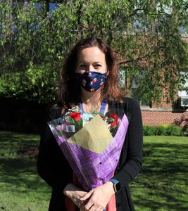 Photo of Molly Dennis holding bouquet of flowers outside