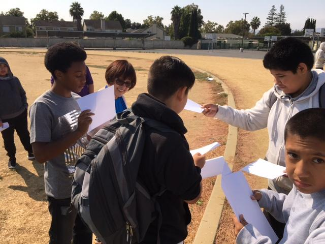 students outside on a track looking at papers they are holding up to the sun to get an image of the eclipse