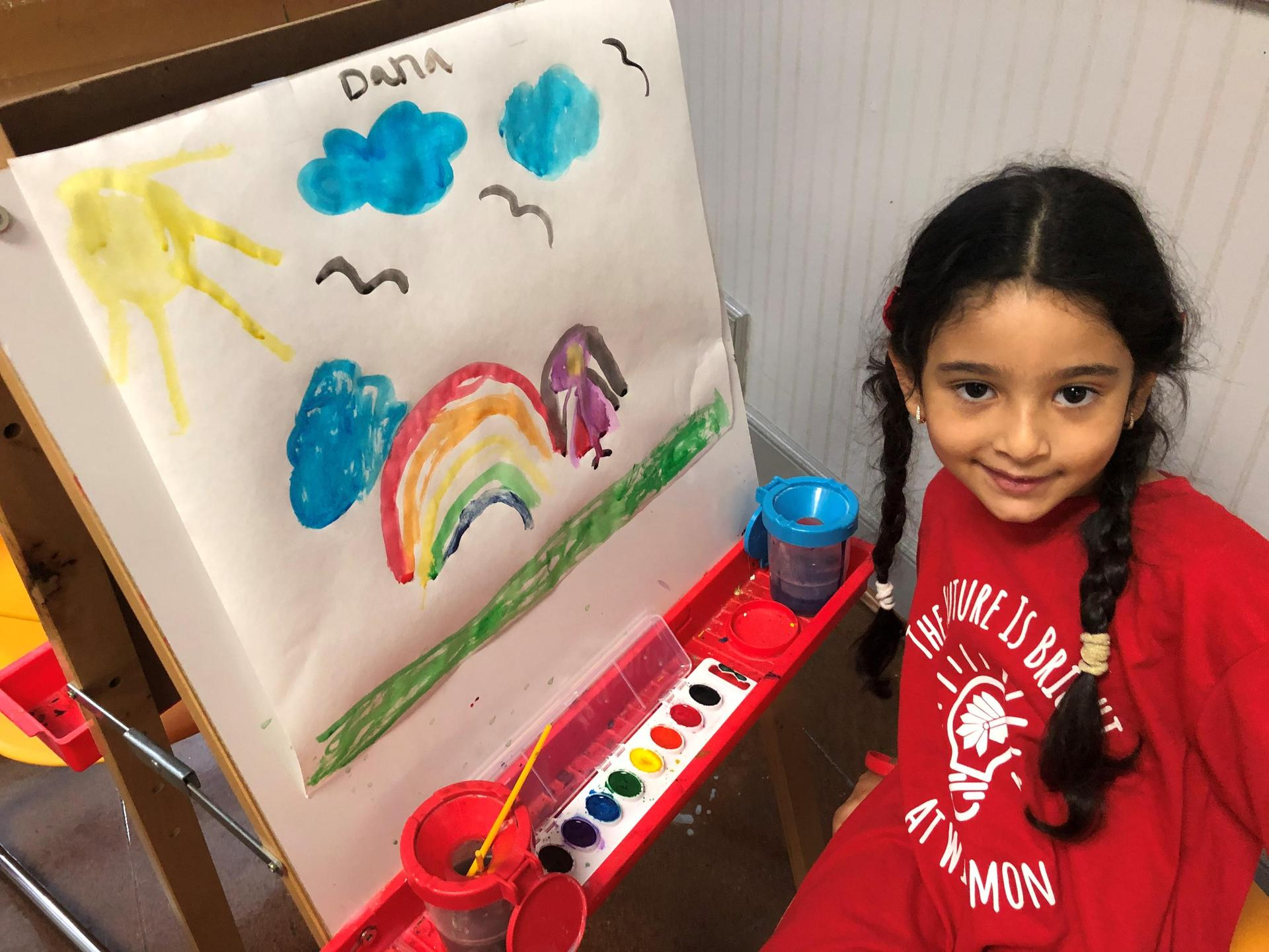 student poses with her watercolor painting on an easel