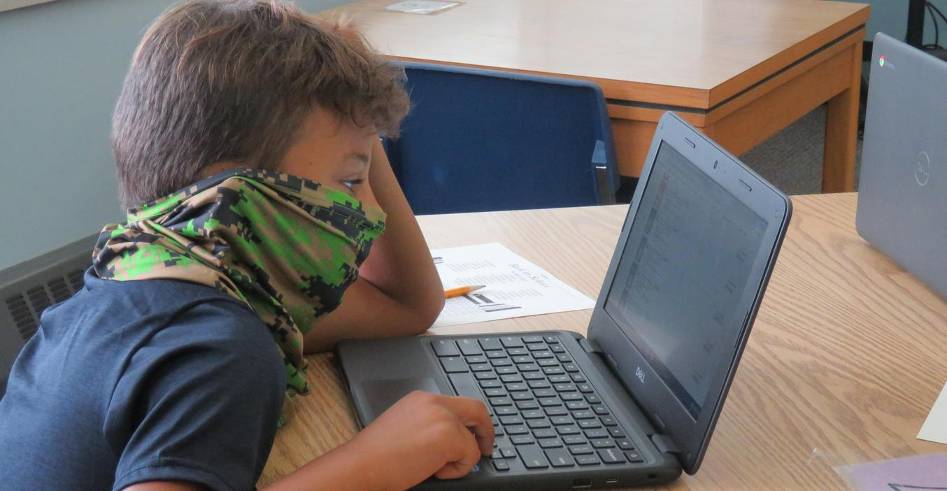 Page Elementary students use their Chromebooks to look up books in the school library.