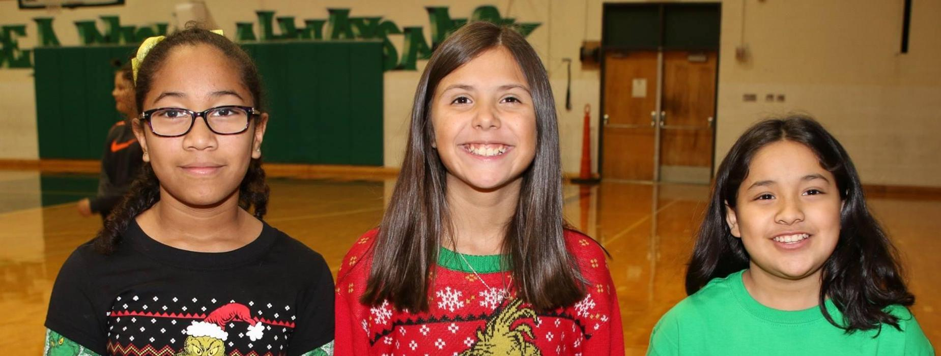 3 students with Grinch sweaters