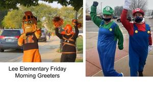 Two Lee Elementary staff members greet students every Friday in different costumes. Here they are Tommy  Trojan, the school mascot, and a TK Cheerleader.