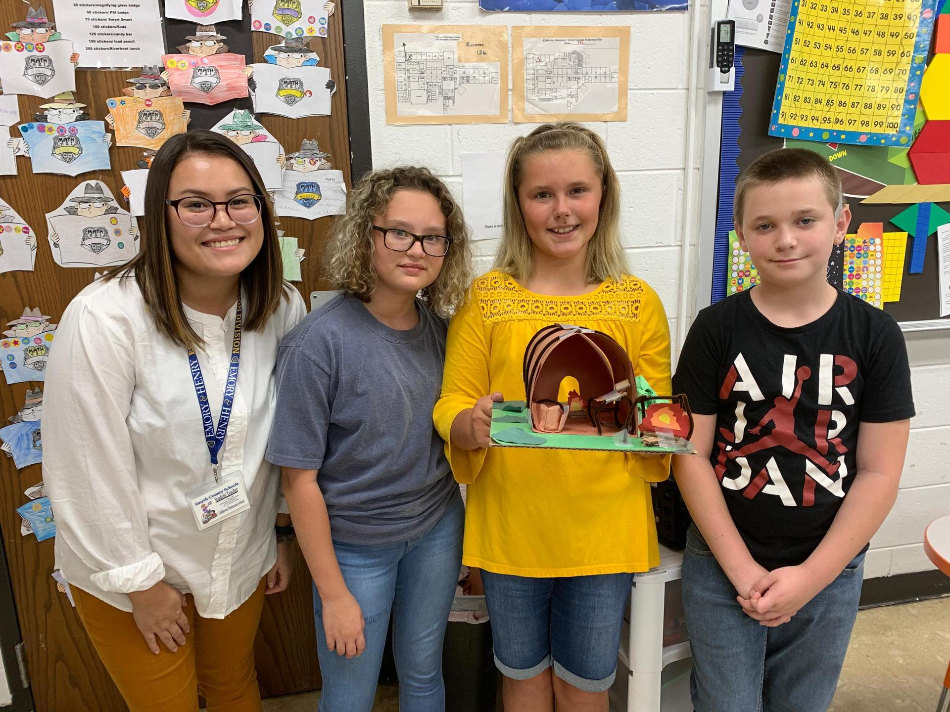 Pictured here, along with a group of students showing their completed longhouse, isstudent-teacher Miss Whitley,