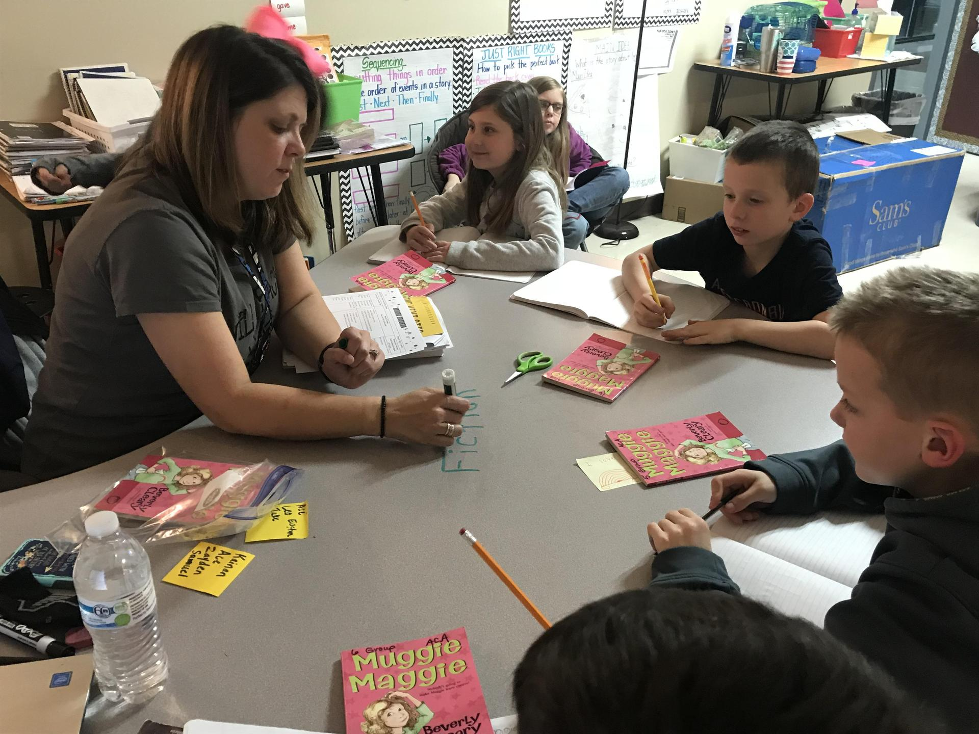students work with a teacher at a table