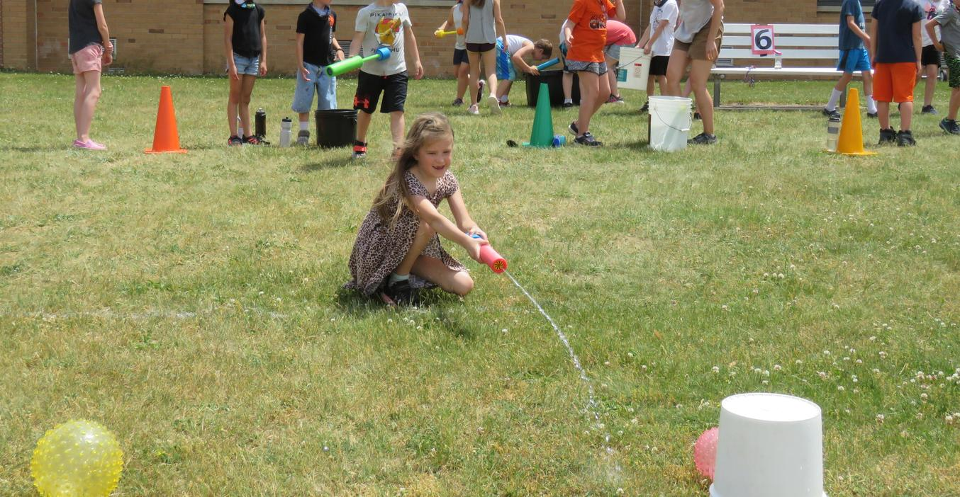 Students take aim with water guns to move a ball.