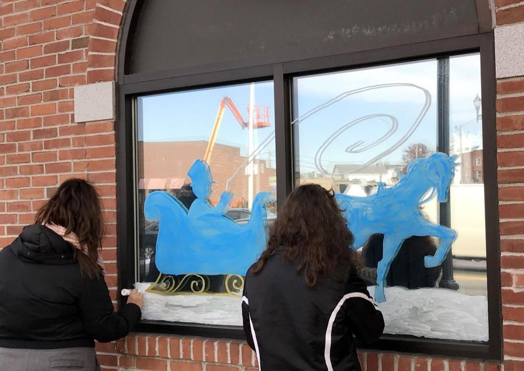 The backs of two students as they decorate a window with an image of a horse-driven sleigh