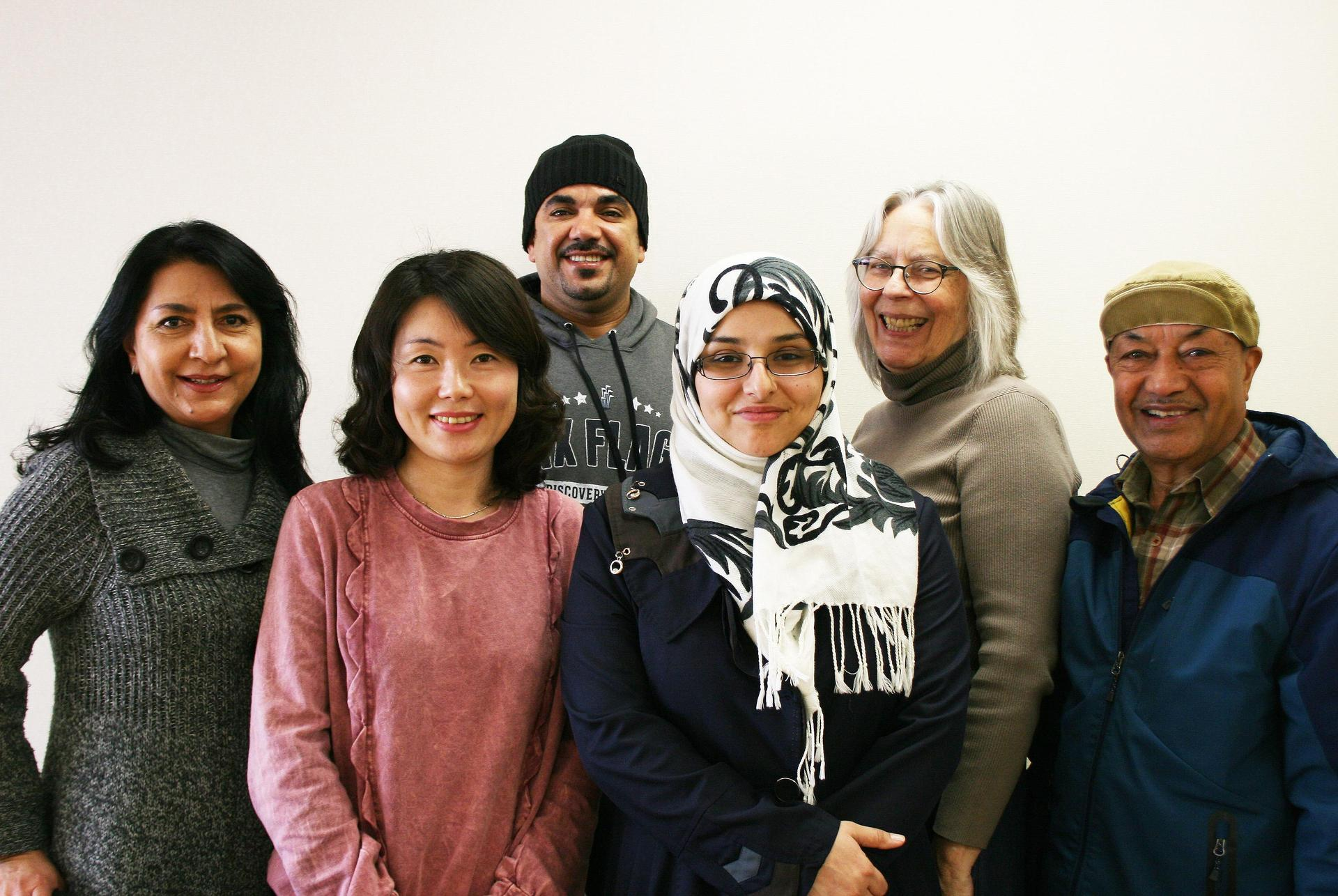 A group of six adult students smiling at the camera.