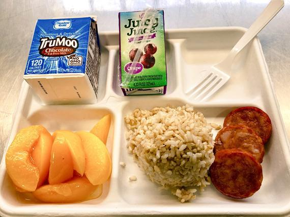 School Lunch plates with milk, peaches, juice, sausage and rice.