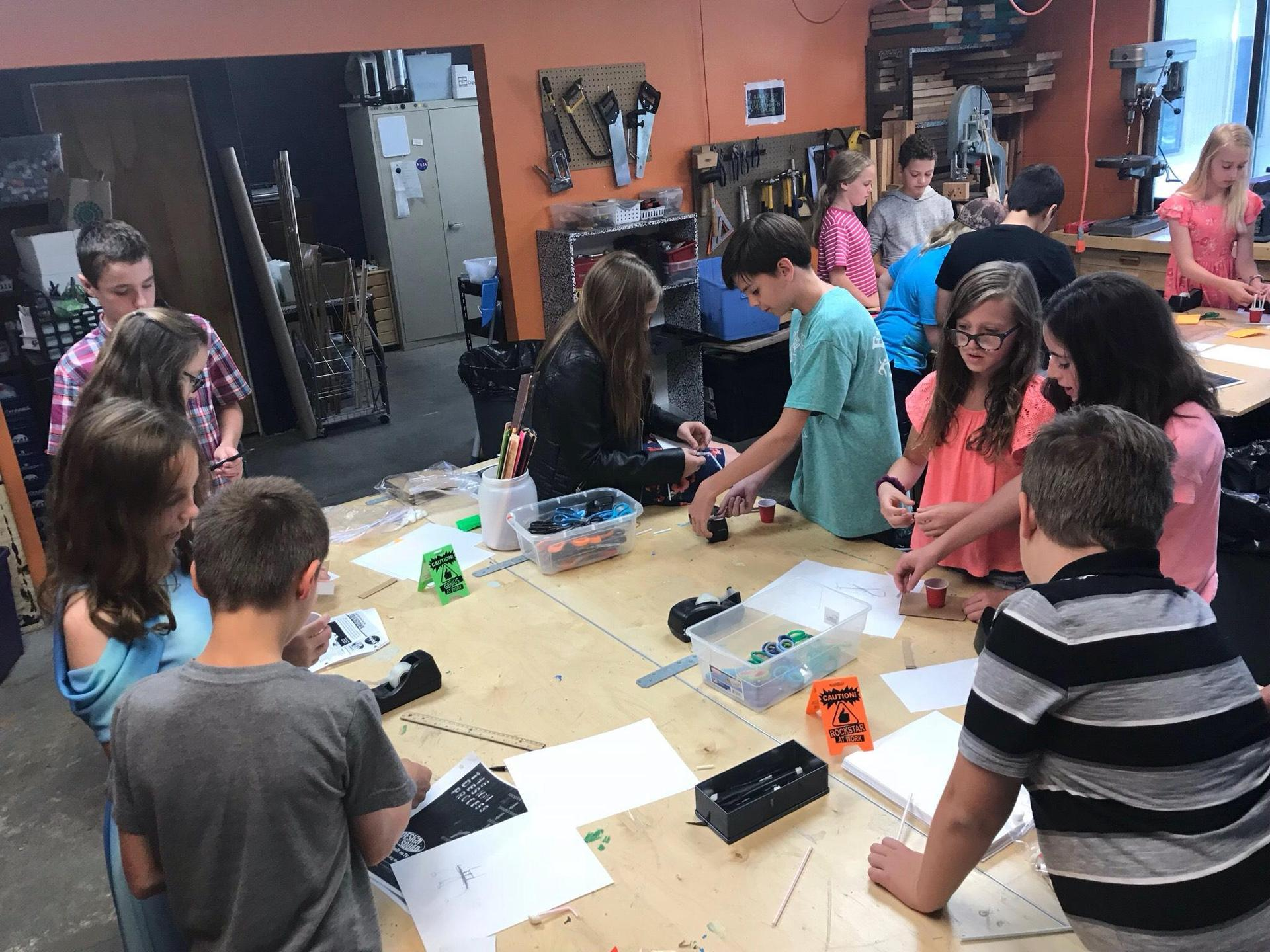 Large group of middle school students collaborate in the makerspace