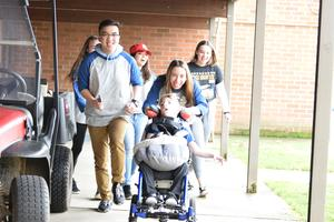 students pushing boy in wheelchair
